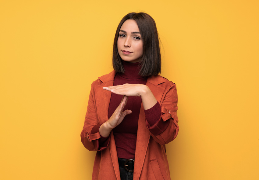 brunette woman in orange coat making the time out hand signal on dark yellow background - boundaries