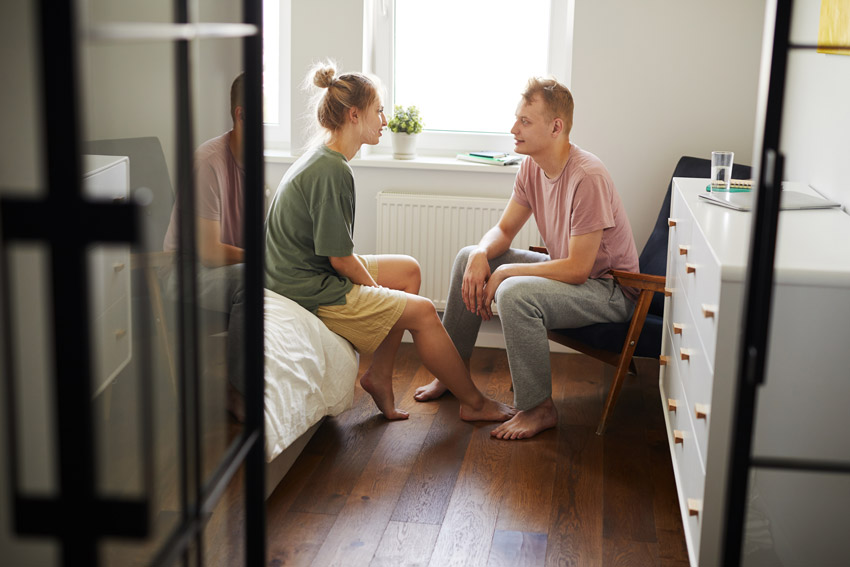 White couple talking in bedroom - support
