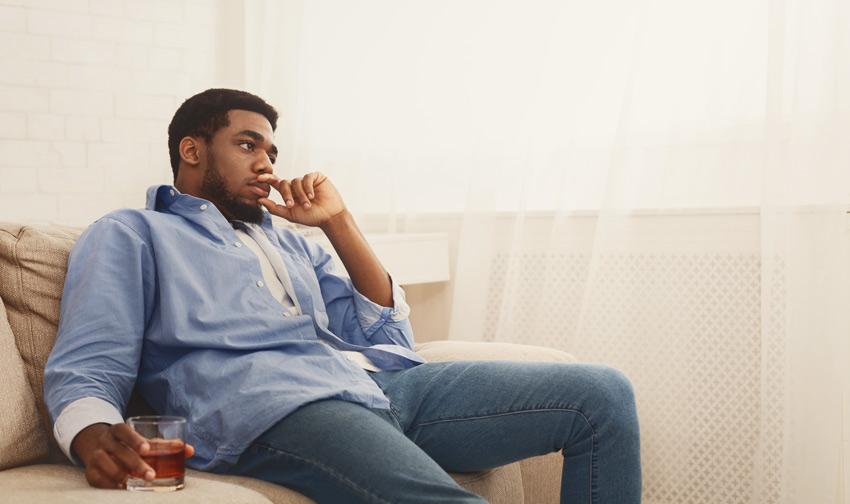 solemn man sitting on couch at home with glass of liquor - relapse occurs