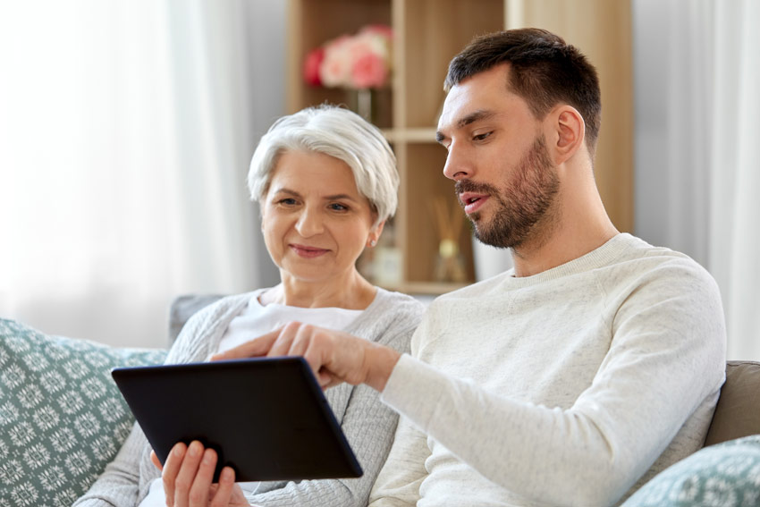 grown son showing mom something on tablet computer - parent