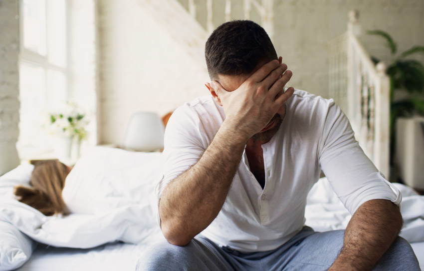 upset man sitting on edge of the bed while wife is asleep - spouse and help