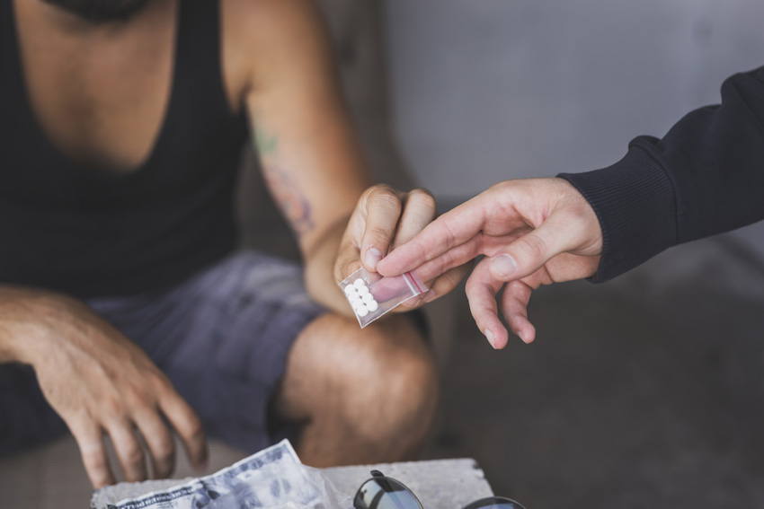 closeup of man buying white tablets in a small baggie - fentanyl addiction