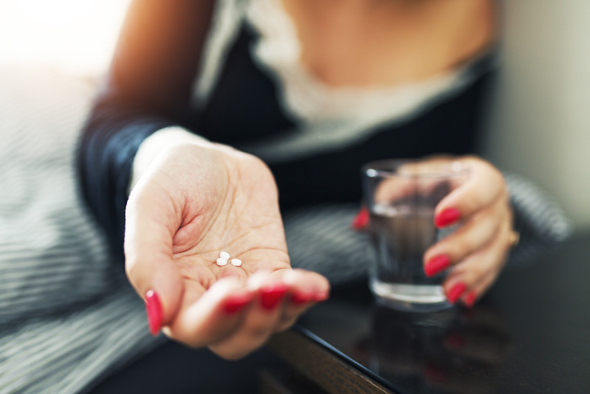 woman with painted nails in night gown taking 3 small white pills with a glass of water - sleeping pill addiction
